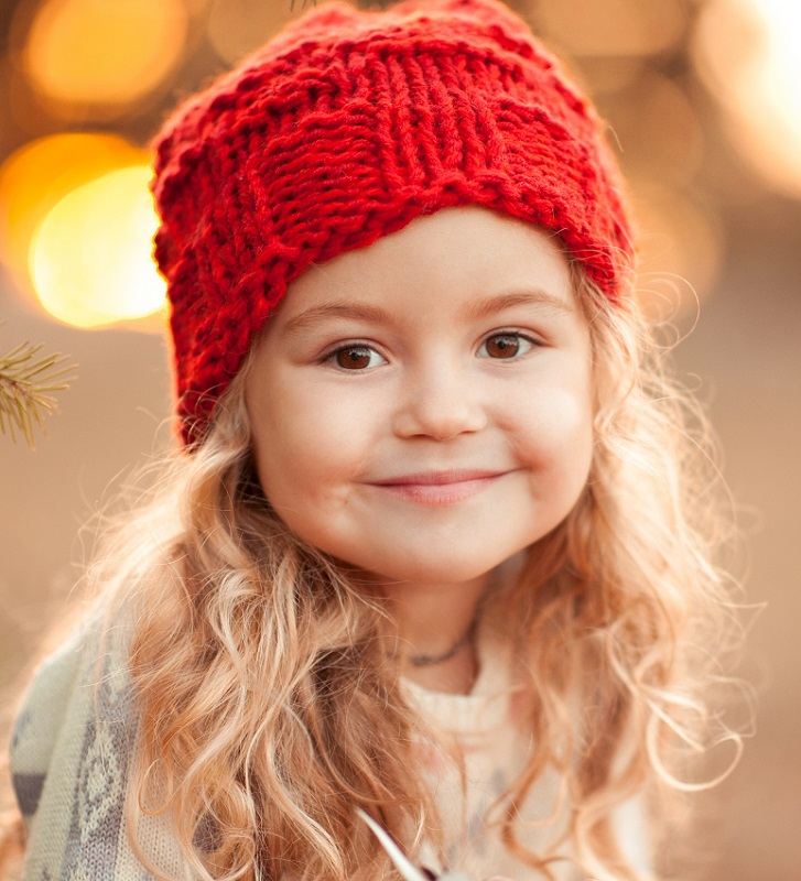 Closeup portrait of smiling child girl smiling looking at camera. Holding toy outdoors. Wearing red knitted hat.