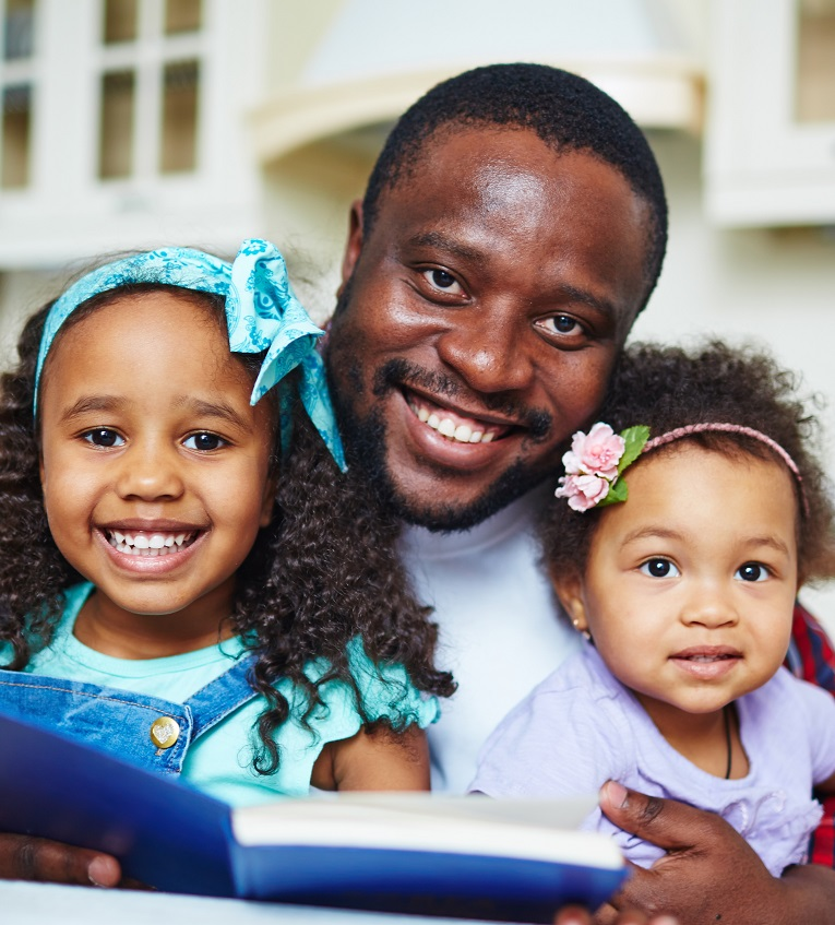 A man reading a book to two children